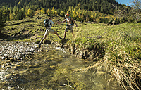 Austria, Tyrol, Tannheimer Tal, two young  hikers crossing water - UUF002129