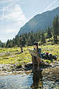 Austria, Tyrol, Tannheimer Tal, two young hikers with having a rest - UU002134