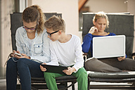 Mother and her two children relaxing with digital tablet, smartphone and laptop on the terrace - PAF001008
