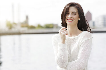 Portrait of smiling young woman wearing white knit pullover - GDF000462
