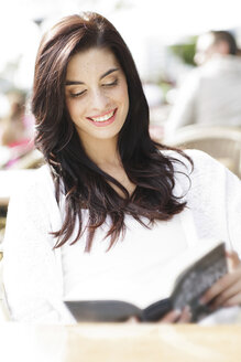 Portrait of happy young woman reading a book at a pavement cafe - GDF000466