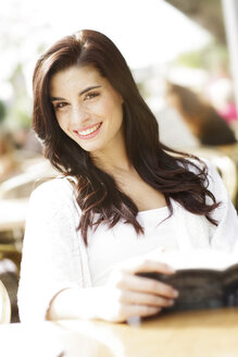 Portrait of happy young woman with book at a pavement cafe - GDF000467