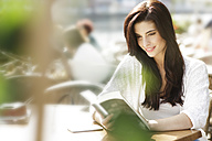 Young woman reading a book at a pavement cafe - GDF000471