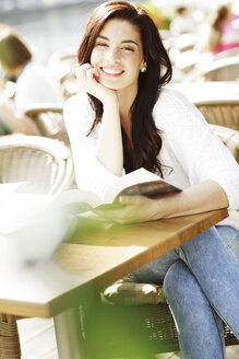 Happy young woman with book at a pavement cafe - GDF000472