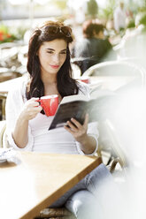 Smiling young woman reading a book at a pavement cafe - GDF000475
