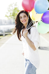 Portrait of happy young woman with a bunch of balloons - GDF000480