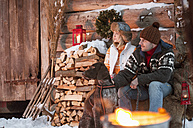 Couple with dog at wooden hut in snow - HHF004945