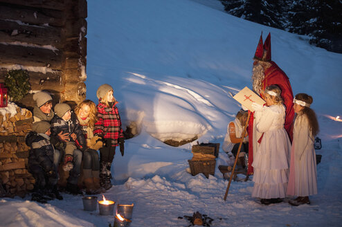 Happy family with angels and Santa Claus at wooden hut in snow - HHF004946