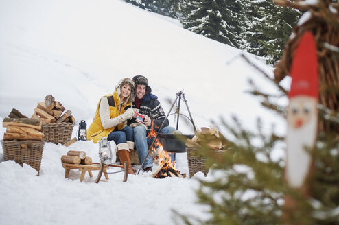 Smiling couple in snow at camp fire - HHF004951