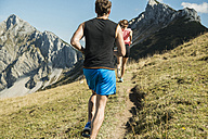 Austria, Tyrol, Tannheim Valley, young couple jogging in mountains - UUF002054