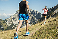 Austria, Tyrol, Tannheim Valley, young couple jogging in mountains - UUF002057