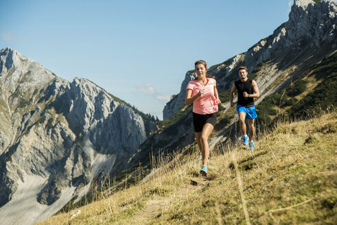 Austria, Tyrol, Tannheim Valley, young couple jogging in mountains - UUF002061