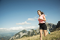 Austria, Tyrol, Tannheim Valley, young woman jogging in mountains - UUF002076