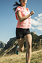 Austria, Tyrol, Tannheim Valley, young woman jogging in mountains - UUF002078