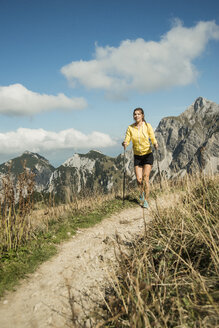 Austria, Tyrol, Tannheim Valley, young woman nordic walking in mountains - UUF002081