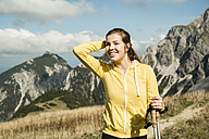Austria, Tyrol, Tannheim Valley, smiling young woman holding nordic walking sticks in mountains - UUF002084