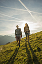 Austria, Tyrol, Tannheimer Tal, young couple hiking on alpine meadow - UUF002326