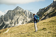 Austria, Tyrol, Tannheimer Tal, hiker with backpack on alpine meadow - UUF002234
