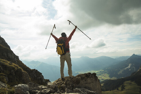 Austria, Tyrol, Tannheimer Tal, young woman with hiking poles cheering on mountain top - UUF002281