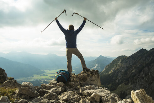 Austria, Tyrol, Tannheimer Tal, young man with hiking poles cheering on mountain top - UUF002284