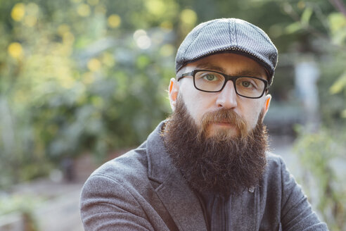 Portrait of beared man wearing glasses and a cap sitting in a garden - FX000075
