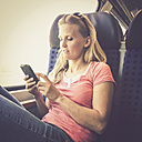 Woman with cell phone in train - SAR000902