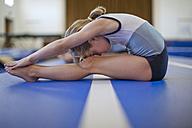 Girl doing gymnastics exercise on floor - ZEF001312