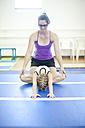 Coach with girl doing gymnastics exercise on floor - ZEF001962