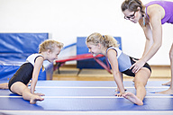 Coach with two girls doing gymnastics exercise on floor - ZEF001315