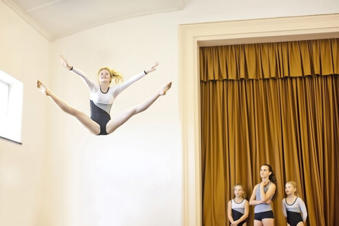 Girl in gymnastics outfit doing aerial jump with three girls watching - ZEF002130