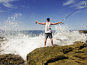 Young man with fishing pole standing at the pacific coast in Mexico, waves breaking on rocky shore. - ABAF001511