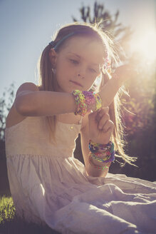 Portrait of little girl sitting at sunlight wearing plenty of loom bracelets - SARF000920