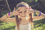 Portrait of smiling ittle girl showing her loom bracelets - SARF000918