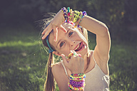 Portrait of little girl with outstretched tongue showing her loom bracelets and rings - SARF000916