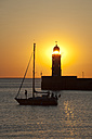 Germany, Bremen, Bremerhaven, Sailing booat, Lighthouse on the pier at sunset - OLEF000043
