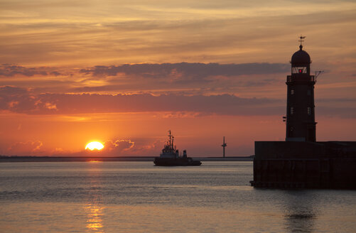 Germany, Bremen, Bremerhaven, Lighthouse on the pier at sunset - OLEF000040