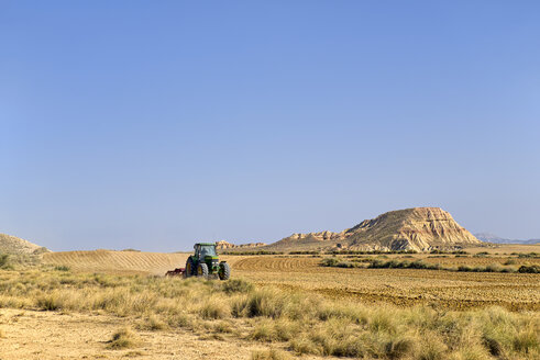 Spain, Navarra, Bardenas Reales, Semi-desert natural region, Tractor on field - LAF001112