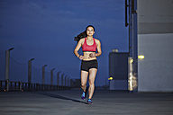 Young female Asian sportswoman jogging at twilight - MAD000093
