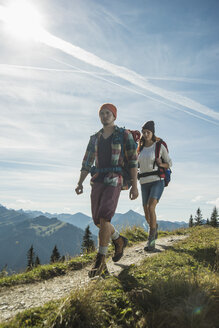 Austria, Tyrol, Tannheimer Tal, young couple hiking on mountain trail - UUF002203