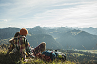 Austria, Tyrol, Tannheimer Tal, young couple having a rest in the mountains - UUF002192