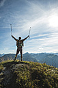 Austria, Tyrol, Tannheimer Tal, young man cheering on mountain top - UUF002182