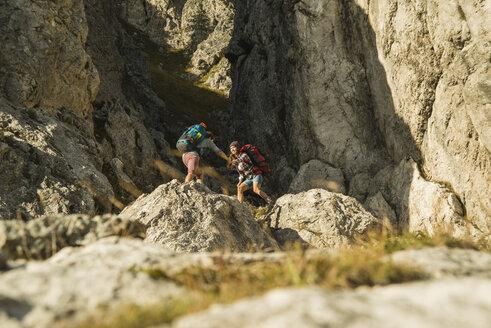 Austria, Tyrol, Tannheimer Tal, young couple hiking at rocks - UUF002153