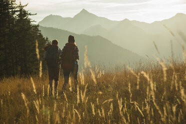 Austria, Tyrol, Tannheimer Tal, young couple hiking in sunlight on alpine meadow - UUF002142
