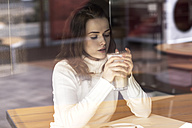 Young woman with Latte Macchiato sitting in a cafe - GDF000510