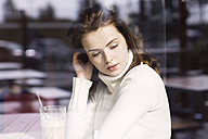 Portrait of young woman with Latte Macchiato sitting in a cafe looking through window pane - GDF000507