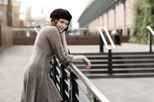 Portrait of young woman wearing beret and knitted dress leaning on a railing - GDF000501
