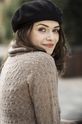 Portrait of smiling young woman wearing beret and knitted dress - GDF000498