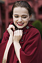 Portrait of smiling young woman wearing red cape - GD000488