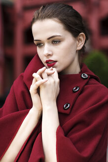 Portrait of daydreaming young woman with red lips wearing red cape - GD000487