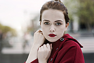 Portrait of young woman with red lips wearing red cape - GD000484